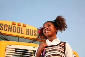 Girl in front of a school bus.